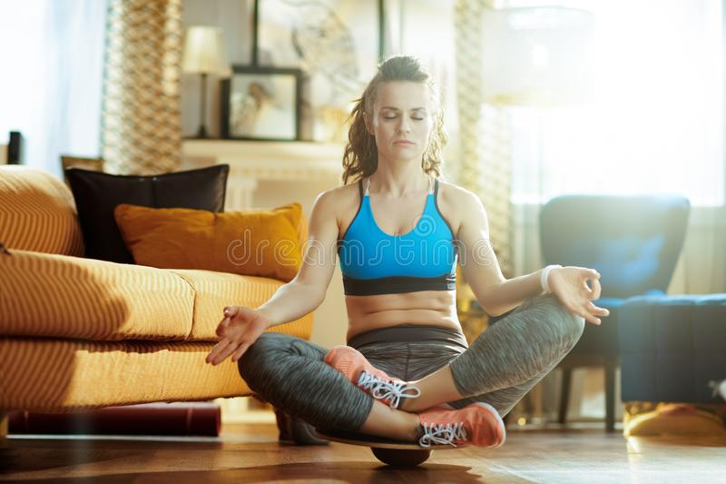Woman in modern living room meditating using balance board. Relaxed active woman in sport clothes in the modern living room meditating using balance board stock photos
