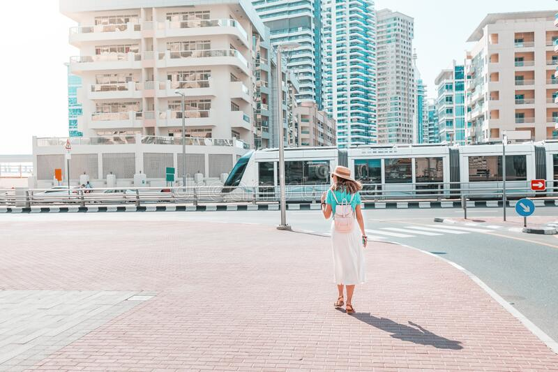 Woman in a modern neighborhood with high-rise buildings goes to the tram stop. Urban transport and passenger and lifestyle. A woman in a modern neighborhood with stock image