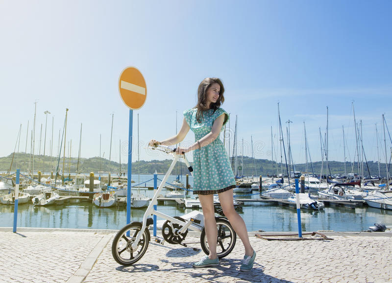 Woman with modern small bicycle. The girl in a polka dot dress with a bike on the seafront with yachts. Horizontal stock image