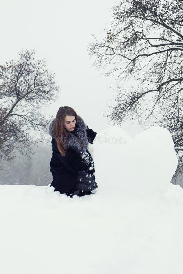 Woman molds a big heart stock photo