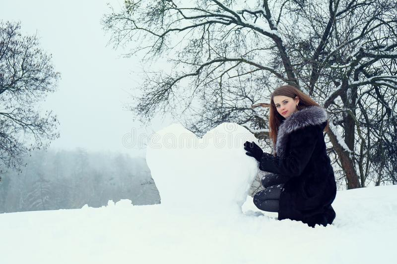 Woman molds a heart of the snow stock photography