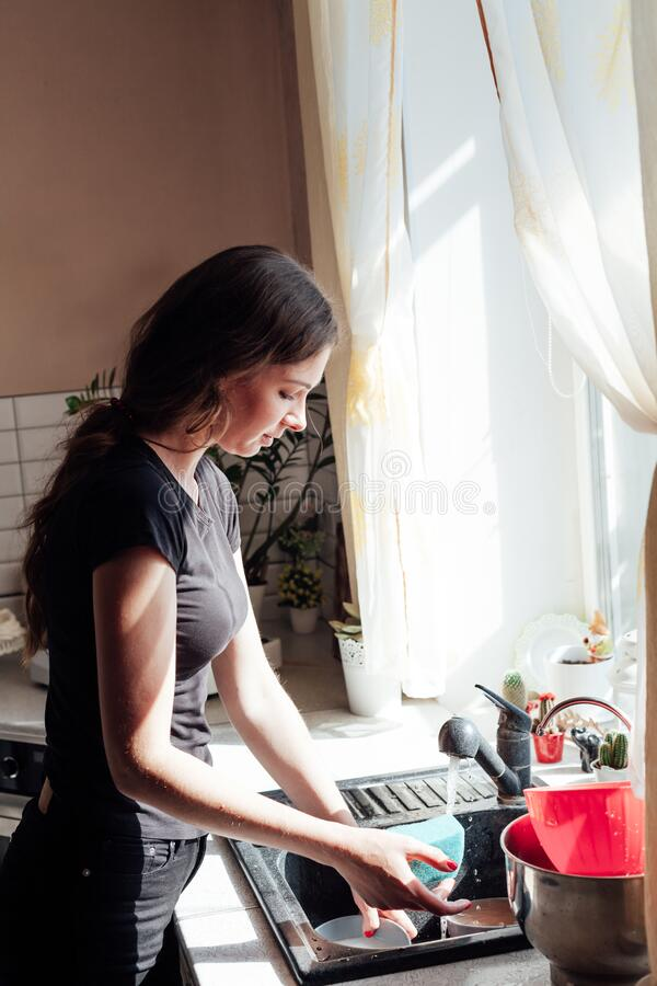 Beautiful woman mom washes dirty dishes in the kitchen royalty free stock image