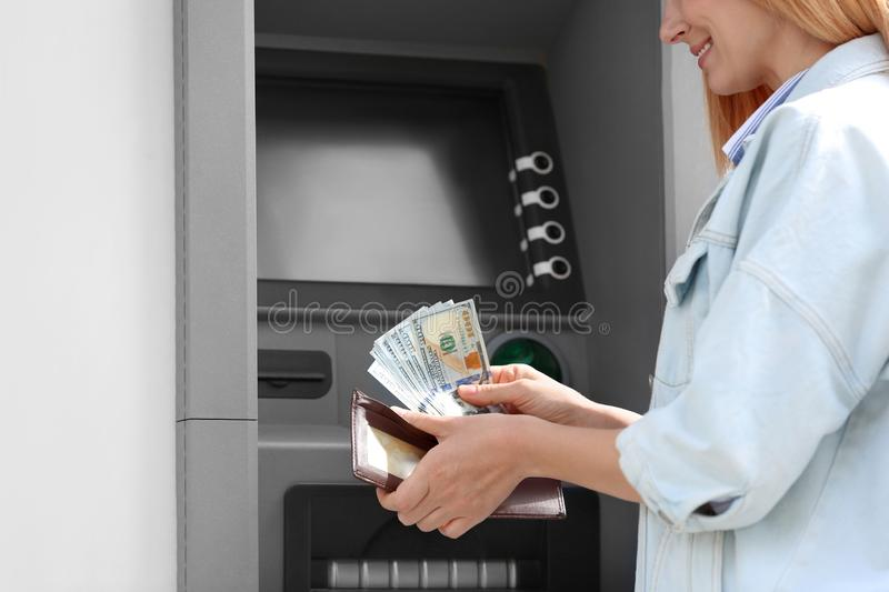 Woman with money near cash machine outdoors stock photography