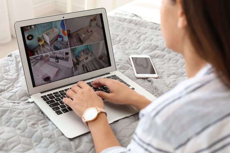 Woman monitoring modern cctv cameras on laptop indoors. Closeup royalty free stock photo