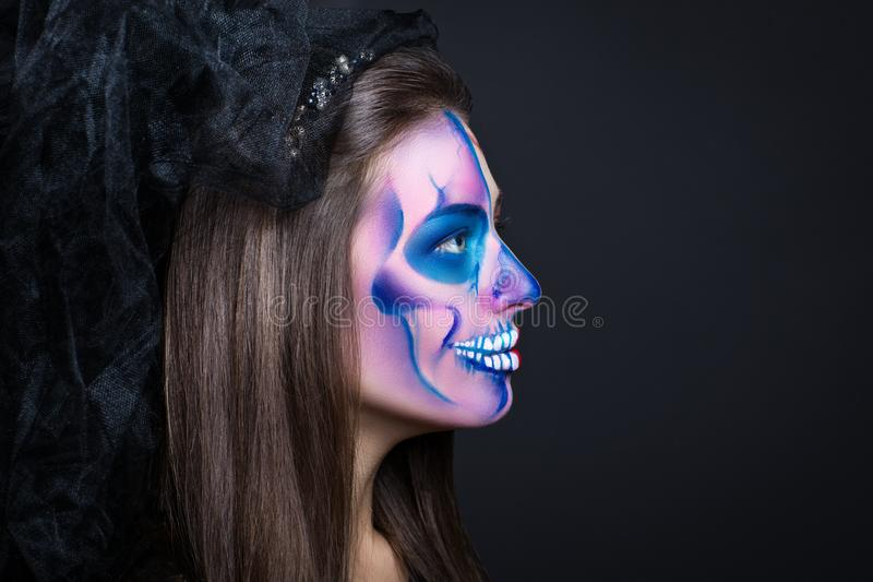 Part of face skull. Woman monster. Creative dark make-up, conceptual idea for Halloween. Eerie nightmare turning into a black vampire, volume spikes body art royalty free stock images