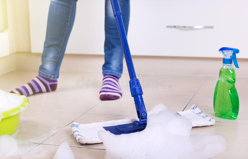 Woman mopping kitchen floor royalty free stock images