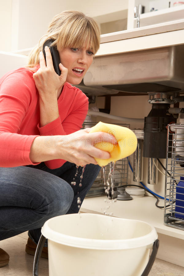 Woman Mopping Up Leaking Sink. On Phone To Plumber royalty free stock image