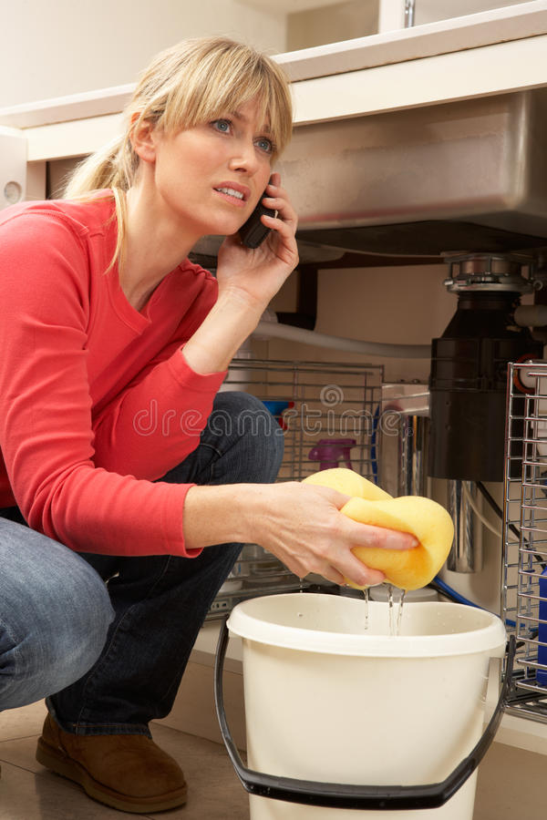 Download Woman Mopping Up Leaking Sink Stock Photo - Image: 18745246