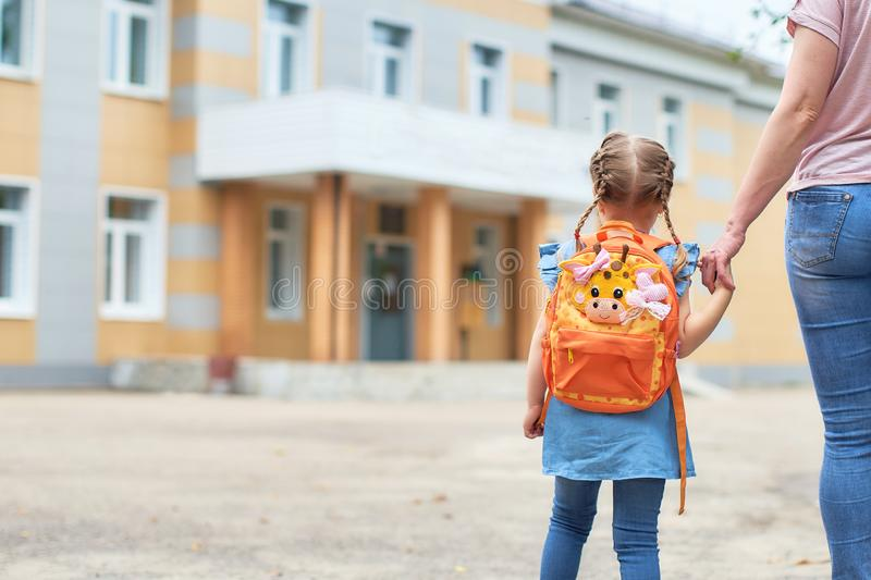 Girl with briefcases near the school stock photo