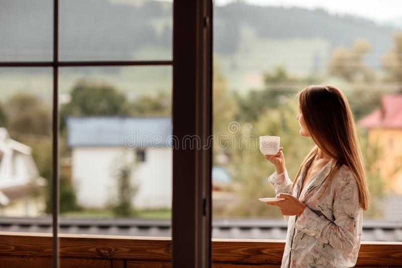 Woman in the morning holding a cup of tea or coffee and looking at the mountains standing near the window stock photography
