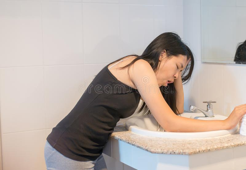 Woman with morning sickness,Pregnant female nausea in toilet. Asian woman with morning sickness,Pregnant female nausea in toilet royalty free stock images