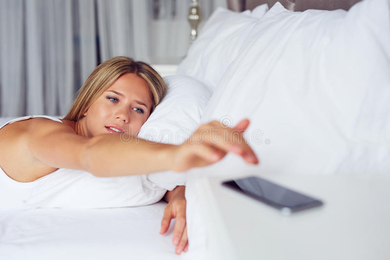 Woman in the morning after waking up with an alarm clock stock photography