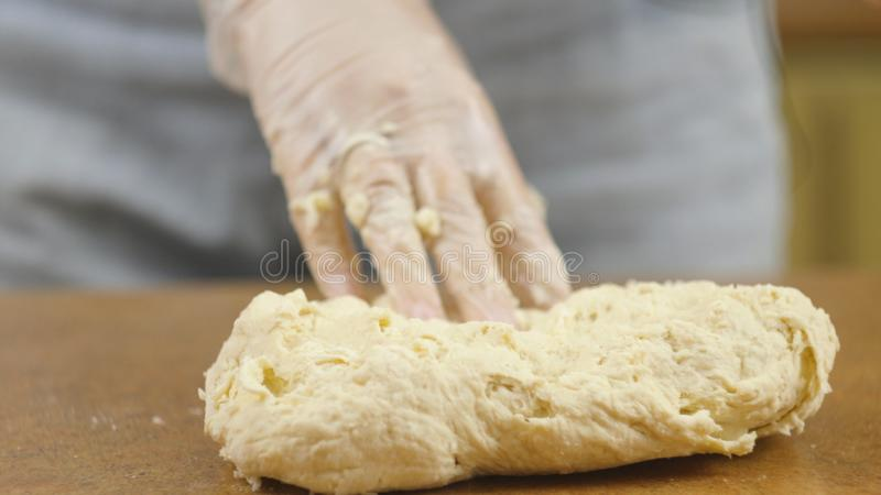 Woman mother or daughter on the kitchen table makes domestic food pizza, hands work and pushing stir knead the dough. Selective focus royalty free stock photo