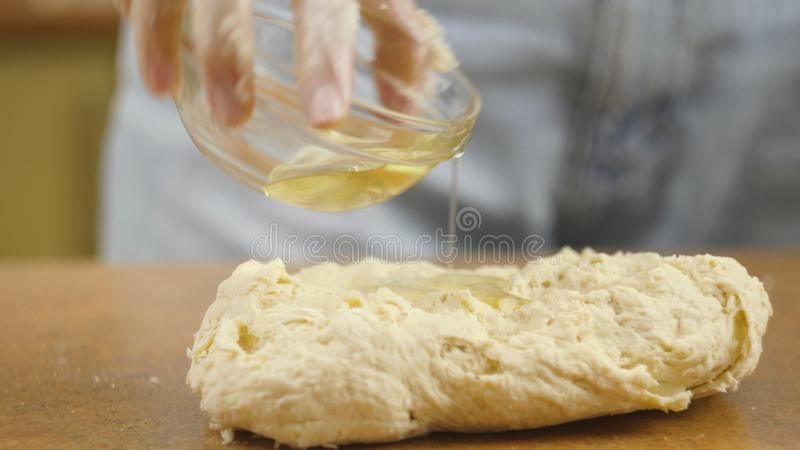 Woman mother or daughter on the kitchen table makes domestic food pizza, hands work and pushing stir knead the dough. Selective focus stock photography