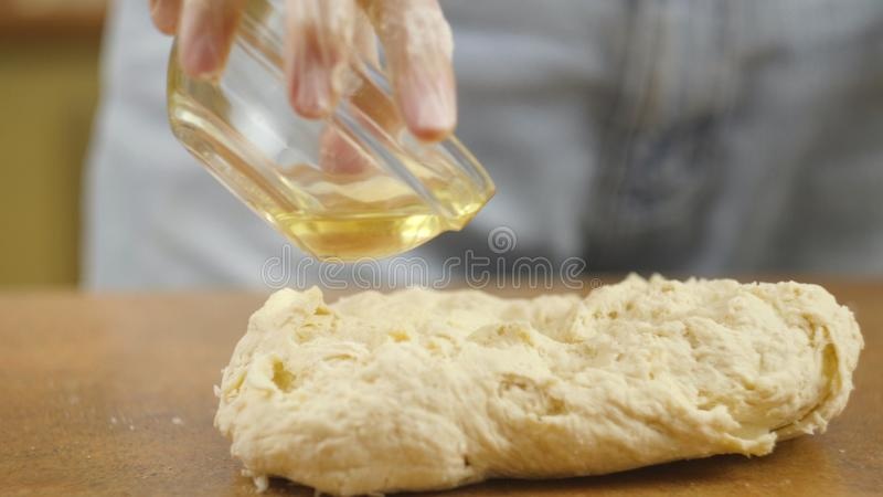 Woman mother or daughter on the kitchen table makes domestic food pizza, hands work and pushing stir knead the dough. Selective focus stock image