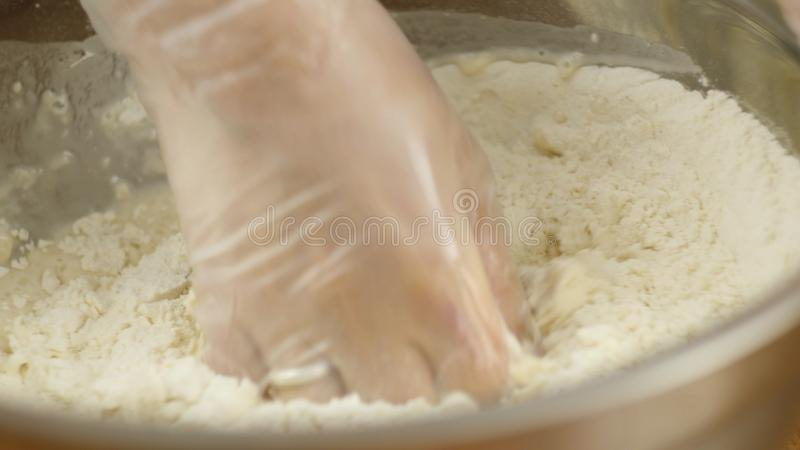 Woman mother or daughter on the kitchen table makes domestic food pizza, hands work and pushing stir knead the dough stock photography