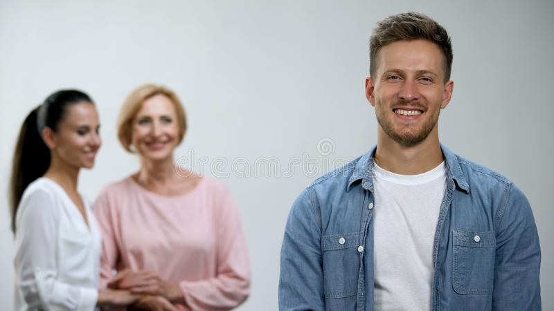 Woman and mother-in-law holding hands, admiring male in family, relations royalty free stock image