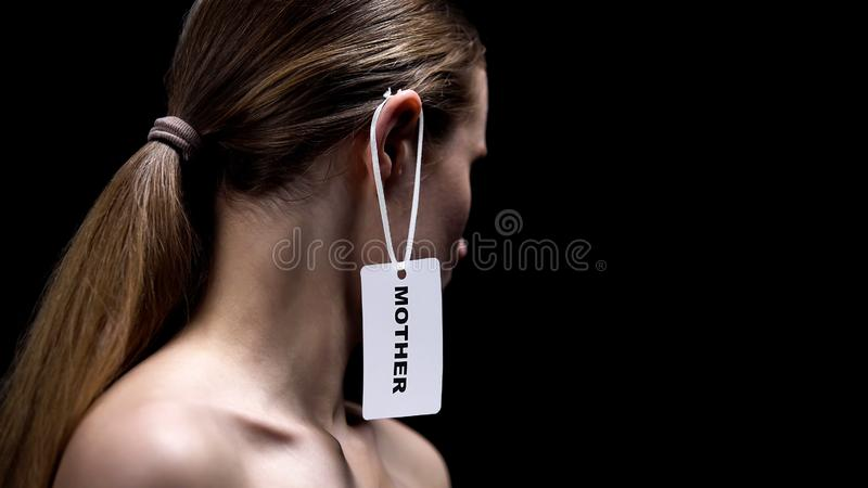 Woman with mother tag on ear against black background, gender stereotypes stock images