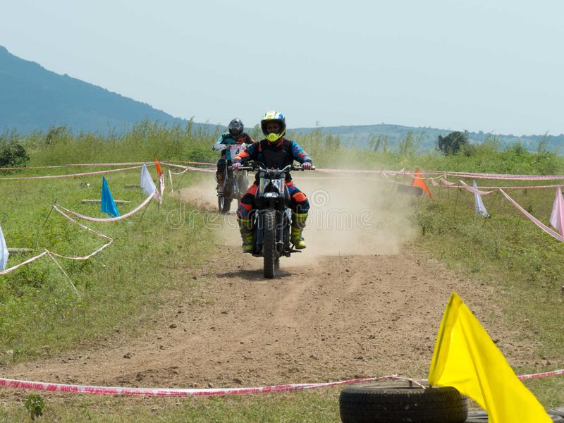 Woman motocross rider overtaking man rider. Woman motocross rider overtaking man rider on dusty dirt track. Event held in India, mix event where male and female royalty free stock photos