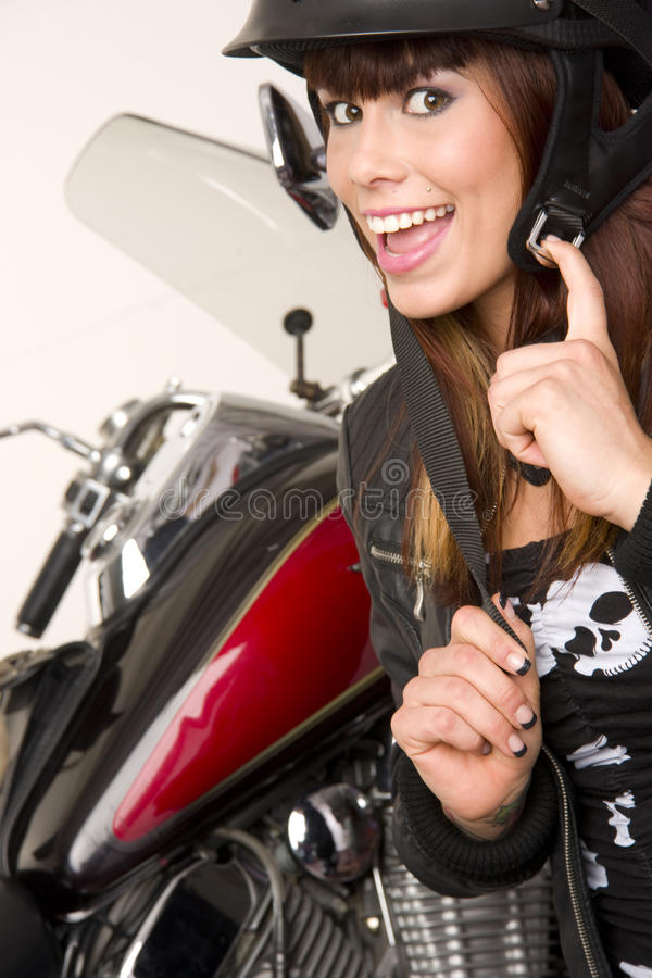 Woman beside Motorcycle putting on gear stock images