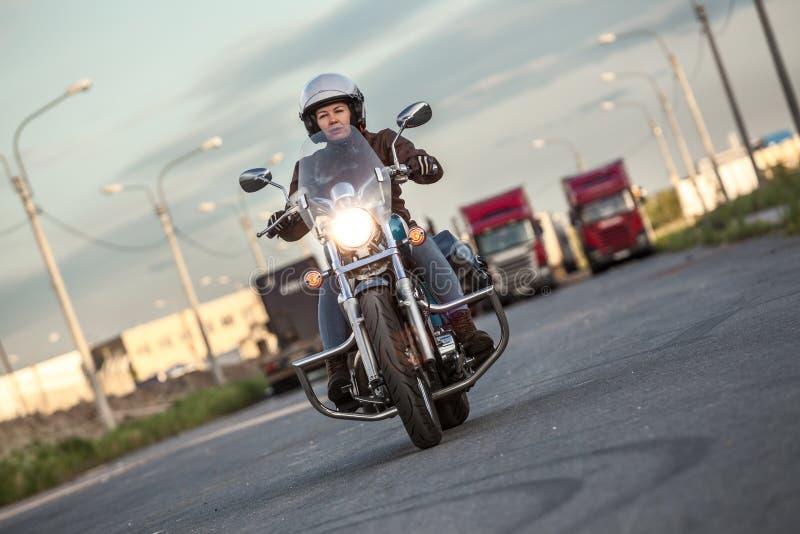 Woman motorcyclist riding on chopper with turning on headlight on asphalt urban road royalty free stock photos
