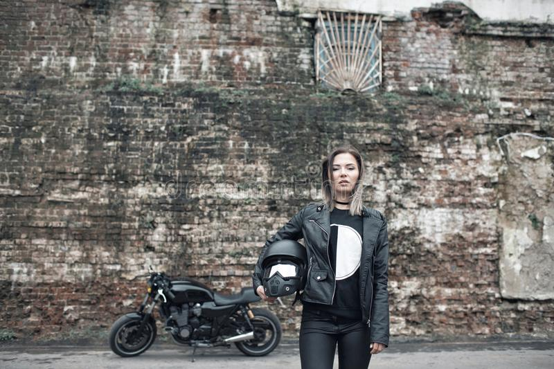 Woman a motorcyclist standing with helmet in hand near her bike, brick wall of garage background. Girl in a leather stock photography