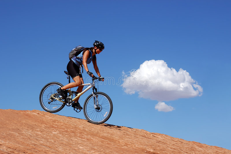 Woman mountain biking royalty free stock photography