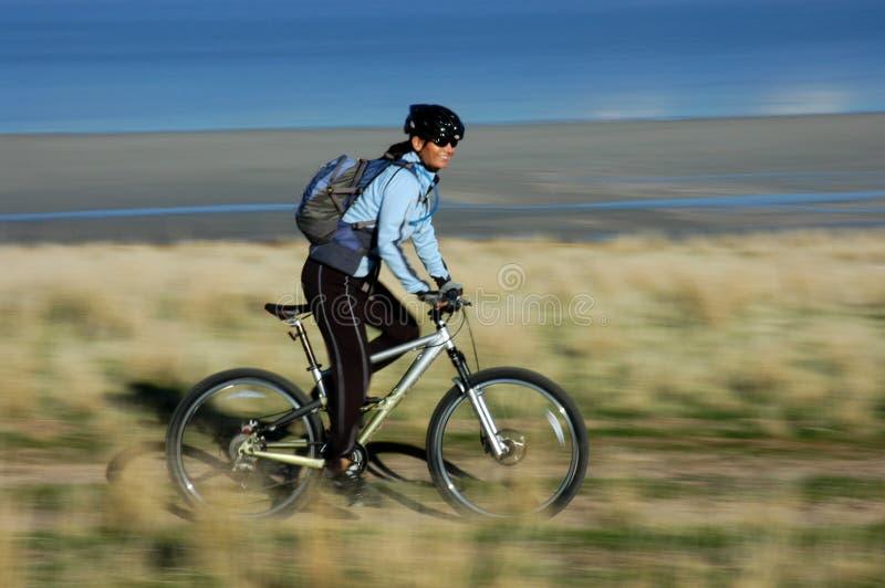 Woman mountain biking stock photo