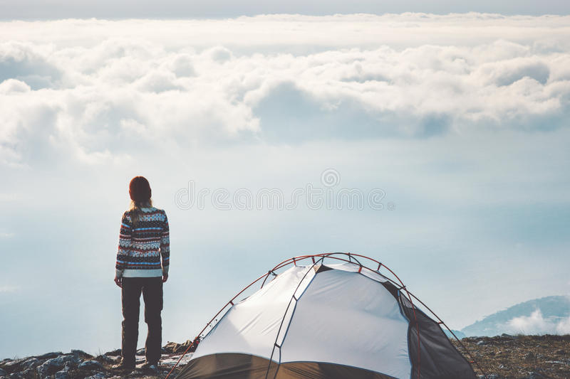 Woman on mountain cliff alone foggy clouds. Landscape on background Travel Lifestyle concept adventure vacations outdoor tent camping royalty free stock photos