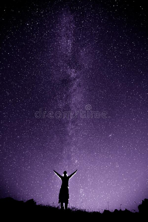 Woman in mountains against night sky with milky way stock images