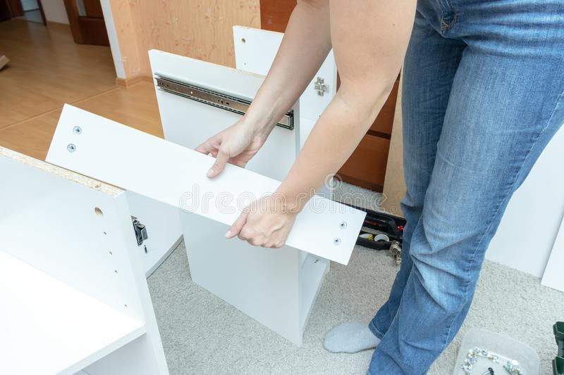 Woman mounting new white furniture, she holding a chipboard plank and putting it to half assembly new dressing table stock photo
