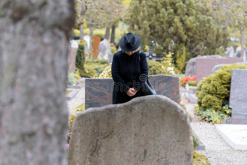 Woman in mourning praying at a graveside. Woman in mourning dressed in full black praying at a graveside standing with her head bowed as she pays respects to a stock images