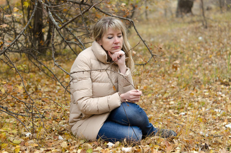 A woman mourns forty years in the autumn forest stock photo