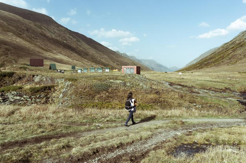Woman moves along a mountain path to a climbers` asylum. In the Caucasus mountains, Russia, reserve royalty free stock photo