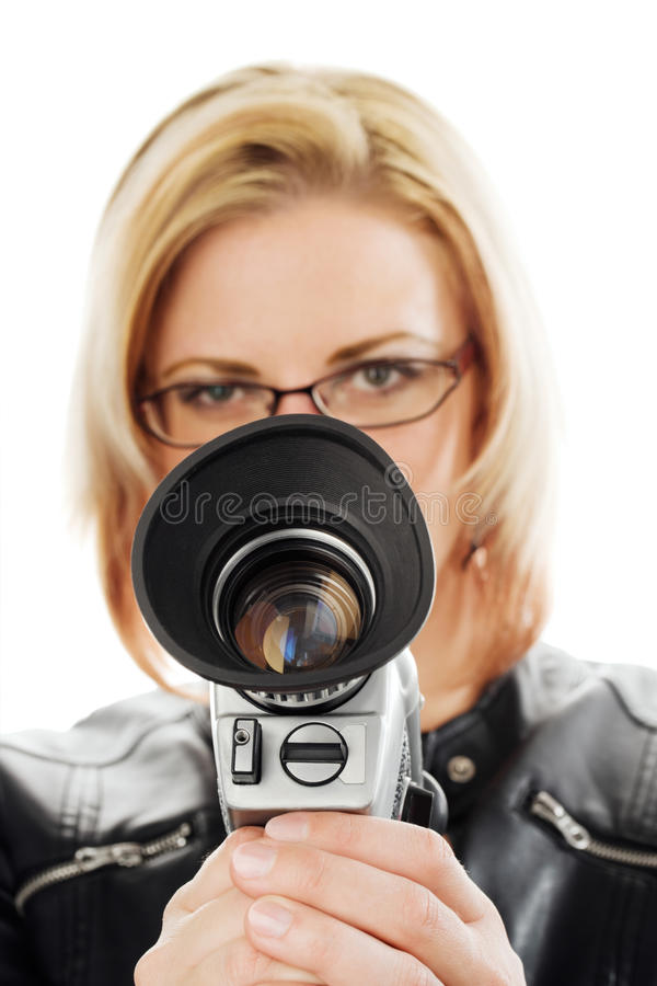 Woman with movie camera. Young woman holding an old movie camera in front of her face. Studio shot against a white background royalty free stock image