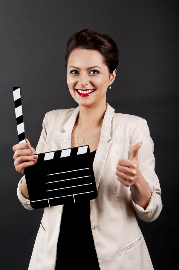 Woman with movie clap thumb up. Woman with movie clap over black background royalty free stock image