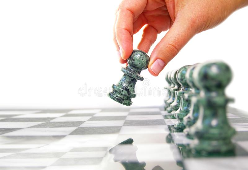 Woman moving a chess piece ahead royalty free stock photo