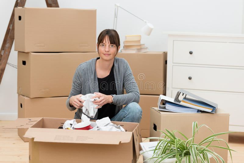 Woman moving house packing her belongings royalty free stock photo