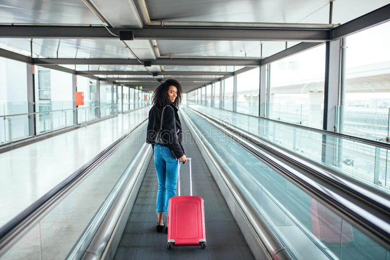 Woman in the moving walkway at the airport with a pink suitcase. stock photo