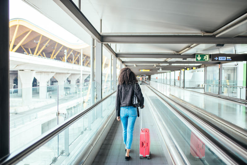 Woman in the moving walkway at the airport with a pink suitcase. royalty free stock image