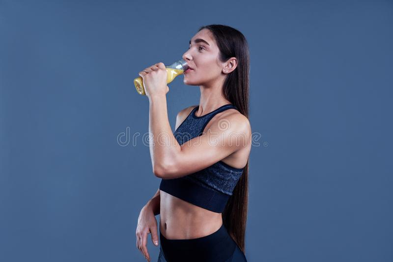 Woman with muscular body in sports clothing with orange juice after workout on grey background. Image with space for text. royalty free stock image