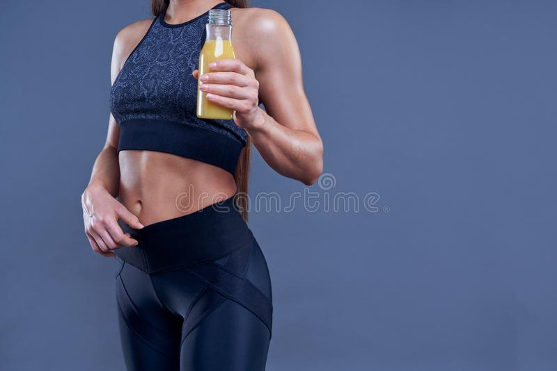 Woman with muscular body in sports clothing with orange juice after workout on grey background. Image with space for text. stock image