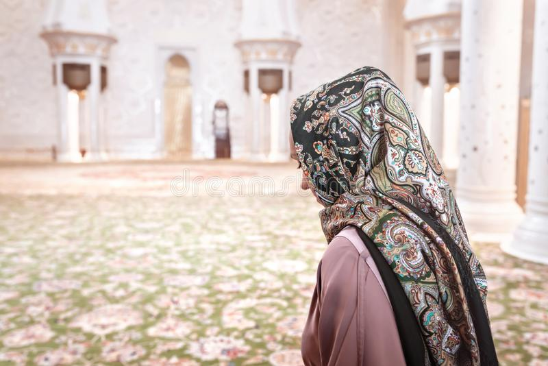 Woman in Muslim prayer room in mosque. Young lady wearing headscarf. Traditional carpet and Arab architecture. stock photography