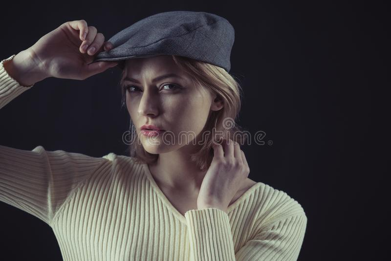 Woman on mysterious face wears kepi, dark background. Blonde lady looks like suspicious detective. Female logic concept royalty free stock photo