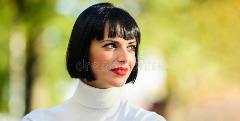 Woman mysterious with red lips makeup face defocused background close up. Makeup bright accent on lips. Red lipstick. Makeup suits her. Perfect makeup for stock image