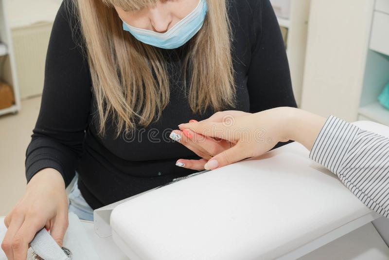 Woman in a nail salon receiving a manicure by a beautician stock images