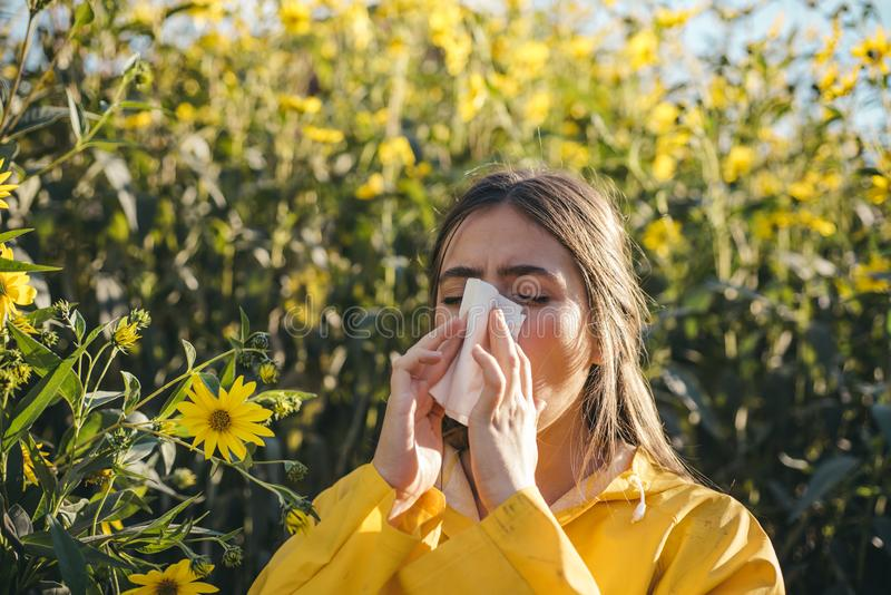 Woman with napkin fighting blossom allergie outdoor. Portrait of an allergic girl surrounded by seasonal flowers in royalty free stock image
