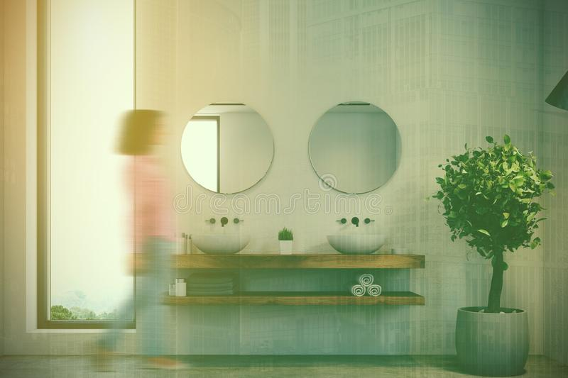 Narrow window bathroom, double sink toned. Woman in a narrow window bathroom interior with a concrete floor, white walls, a double sink and two round mirrors. A stock photos