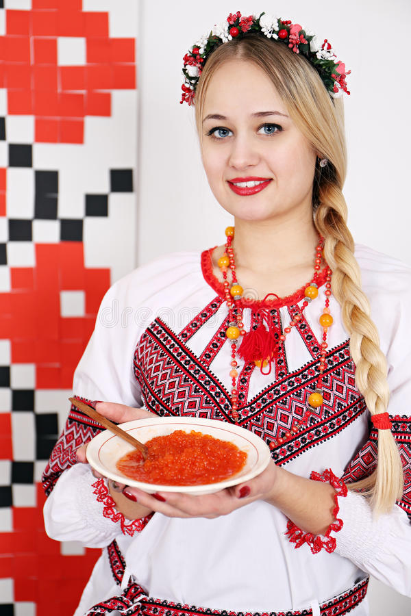 Woman in national costume holding a plate of caviar royalty free stock image