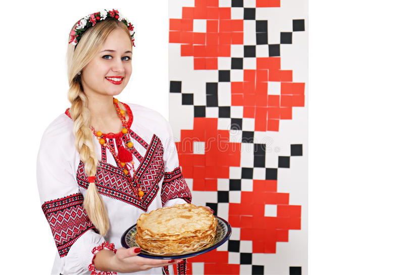Woman in national costume holding a plate of pancakes stock photography